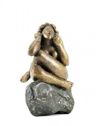Figura feminina sentada sobre rocha